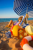 Happy child sitting on the sunbed. Funny kid at the beach. Summer vacation concept Stock Photography