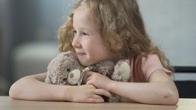 Happy child sitting at the table, holding teddy bear and smiling. Childhood. Stock footage stock video footage