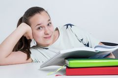 Happy child sitting at the table reading a book. royalty free stock photo