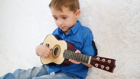 A happy child is sitting on a white sofa playing a children`s acoustic guitar and singing. Slow motion stock video