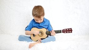 A happy child is sitting on a white sofa and playing the guitar for children stock video