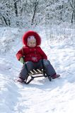 Happy child on sled in winter. Winter photo of a child in the park Stock Photo