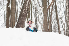 Happy child sledging from a snowy hill Royalty Free Stock Images