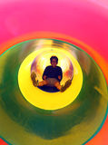 Happy child slides in multicolored tunnel slide in the playgroun Stock Image