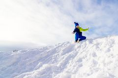 Happy child sliding from little snowy hill Stock Photo