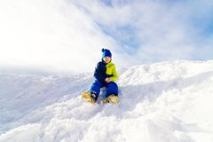 Happy child sliding from little snowy hill Stock Images