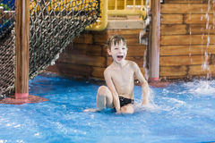 Happy child in a small wading pool. Looking up at the camera and smiling Stock Photo