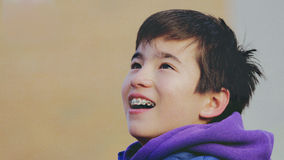 Happy child smiles with braces. Portrait of a child smiling looking up and showing braces Royalty Free Stock Images