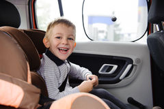 Happy child smiling in car seat Royalty Free Stock Photography