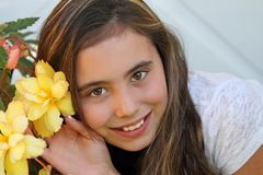 Happy child smiling near illumination begonia flowers Royalty Free Stock Photography