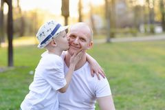 Happy child son kissing father. Father`s Day. Happy family in the park Royalty Free Stock Photo