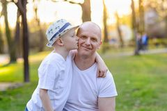 Happy child son kissing father. Father`s Day. Happy family in the park Stock Images