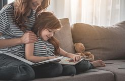 Happy child spending leisure drawing with her mom at home royalty free stock image