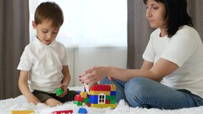 Happy child spends time playing with the nanny, mom sitting on the bed in the room. A mother and a little boy build from