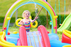 Happy child splashing in inflatable garden pool stock photography