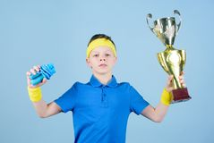 Happy child sportsman hold champion cup trophy. Fitness and diet. Energy. Gym workout of teen boy winner. Success trophy. Childhood activity. Sport and health stock photos