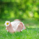 Happy child in spring park. Happy child outdoors. Kid having fun in spring park. Baby lying on green grass Royalty Free Stock Image