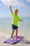 Happy Child Standing on Boogie Board in Ocean Stock Image