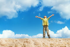 Happy child standing with hands raised up over sky Stock Photo