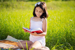 Happy child studying on nature. With books Royalty Free Stock Photography