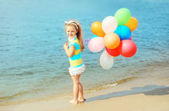 Happy child on summer beach with colorful balloons Royalty Free Stock Images