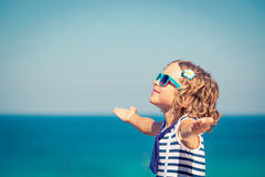 Happy child on summer vacation. Happy child with open hands against blue sea and sky background. Kid having fun on summer vacation. Freedom and imagination Stock Image