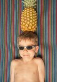 Happy child with sunglasses and pineapple in head Royalty Free Stock Photography