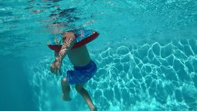 Happy child having fun in blue clear pool. Happy child swimming in blue clear pool with sun rays reflections in the water stock video