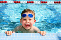 Happy child in a swimming pool. Smiling six year old boy in a sunny swimming pool Stock Photography