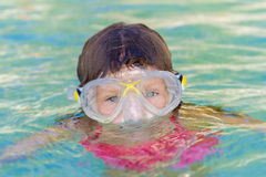 Happy child swimming in the sea in a floating ring on trop Royalty Free Stock Image