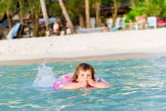 happy child swimming in the sea in a floating ring on trop Royalty Free Stock Photo