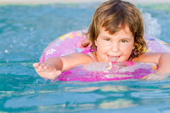 Happy child swimming in the sea in a floating ring on trop Stock Images