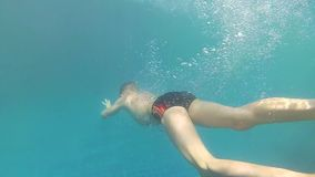 Happy child swims with enjoyment under the water in the pool stock video footage