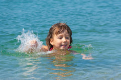 Happy child swims in sea Stock Images
