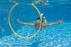 Happy child swims underwater in swimming pool Stock Photos