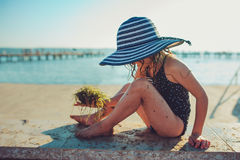 Happy child in swimsuit and hat relaxing on the summer beach and getting some tan. Warm weather, cozy mood. Traveling on summer vacation Royalty Free Stock Photography