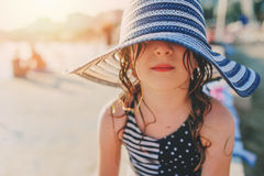Happy child in swimsuit and hat relaxing on the summer beach and getting some tan. Warm weather, cozy mood. Traveling on summer vacation Stock Image