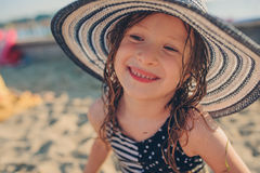 Happy child in swimsuit and hat relaxing on the summer beach and getting some tan. Warm weather, cozy mood. Traveling on summer vacation Stock Photo