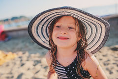 Happy child in swimsuit and hat relaxing on the summer beach and getting some tan. Warm weather, cozy mood. Traveling on summer vacation Stock Photography