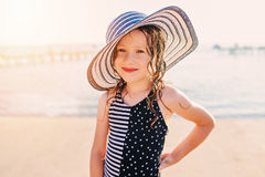 Happy child in swimsuit relaxing on the summer beach and getting some tan. Warm weather, cozy mood. Traveling on summer vacation Royalty Free Stock Photos