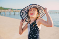 Happy child in swimsuit relaxing on the summer beach and getting some tan. Warm weather, cozy mood. Traveling on summer vacation Stock Photography