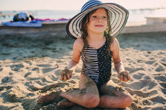 Happy child in swimsuit relaxing on the summer beach and getting some tan. Warm weather, cozy mood. Traveling on summer vacation Royalty Free Stock Photo