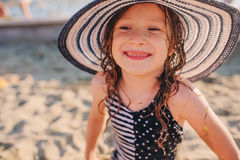 Happy child in swimsuit relaxing on the summer beach and getting some tan. Warm weather, cozy mood. Royalty Free Stock Photography