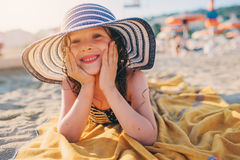 happy child in swimsuit relaxing on the summer beach, lying on towel and getting some tan. Warm weather, cozy mood. Traveling on s Royalty Free Stock Images