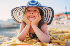 Happy child in swimsuit relaxing on the summer beach, lying on towel and getting some tan. Warm weather, cozy mood. Traveling on s. Ummer vacation.  Selective Stock Image