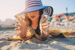 Happy child in swimsuit relaxing on the summer beach, lying on towel and playing with sand. Warm weather, cozy mood. Traveling on Stock Images