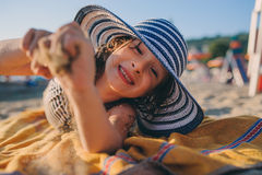 Happy child in swimsuit relaxing on the summer beach, lying on towel and playing with sand. Warm weather, cozy mood. Traveling on Stock Image