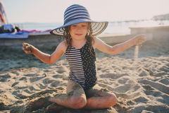 Happy child in swimsuit relaxing on the summer beach and playing with sand. Warm weather, cozy mood. Stock Photo
