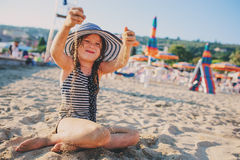 Happy child in swimsuit relaxing on the summer beach and playing with sand. Warm weather, cozy mood. Stock Image