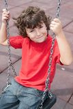 Happy child on the swing. With red shirt Stock Photography